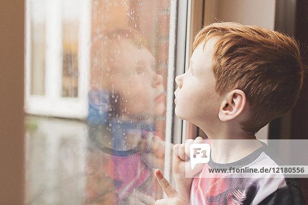 Boy looking at the rain on windowpane