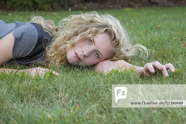 Blonde teenage girl outdoors  lying on the grass.