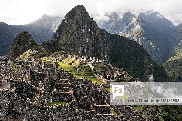 View of the Machu Picchu landscape. Machu Picchu is a city located high in the Andes Mountains in modern Peru. It lies 43 miles northwest of Cuzco at the top of a ridge,  hiding it from the Urabamba gorge below. The ridge is between a block of highland and the massive Huaynac Picchu,  around which the Urubamba River takes a sharp bend. The surrounding area is covered in dense bush,  some of it covering Pre-Colombian cultivation terraces. Machu Picchu stands 2, 430 m above sea-level,  in the middle of a tropical mountain forest,  in an extraordinarily beautiful setting. It was probably the most amazing urban creation of the Inca Empire at its height,  its giant walls,  terraces and ramps seem as if they have been cut naturally in the continuous rock escarpments. The natural setting,  on the eastern slopes of the Andes,  encompasses the upper Amazon basin with its rich diversity of flora and fauna. Embedded within a dramatic landscape at the meeting point between the Peruvian Andes and the Amazon Basin,  the Historic Sanctuary of Machu Picchu is among the greatest artistic,  architectural and land use achievements anywhere and the most significant tangible legacy of the Inca civilization. Recognized for outstanding cultural and natural values,  the mixed World Heritage property covers 32, 592 hectares of mountain slopes,  peaks and valleys surrounding its heart,  the spectacular archaeological monument of â. œLa Ciudadelaâ.(the Citadel) at more than 2, 400 meters above sea level. Built in the fifteenth century Machu Picchu was abandoned when the Inca Empire was conquered by the Spaniards in the sixteenth century. It was not until 1911 that the archaeological complex was made known to the outside world.