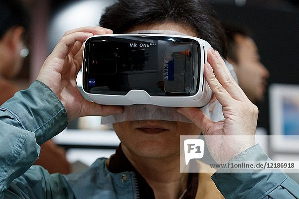 March 3  2018  Yokohama  Japan - A man tries out a ZEISS VR One Plus (Virtual Reality Headset) at the CP+ Camera & Photo Imaging Show 2018 in Pacifico Yokohama. Japan's largest camera and photo imaging exhibition bring together 1 123 exhibitor booths during the four-day trade show at the Pacifico Yokohama and OSANBASHI Hall. Organizers expect approximately 70 000 visitors until March 4th.