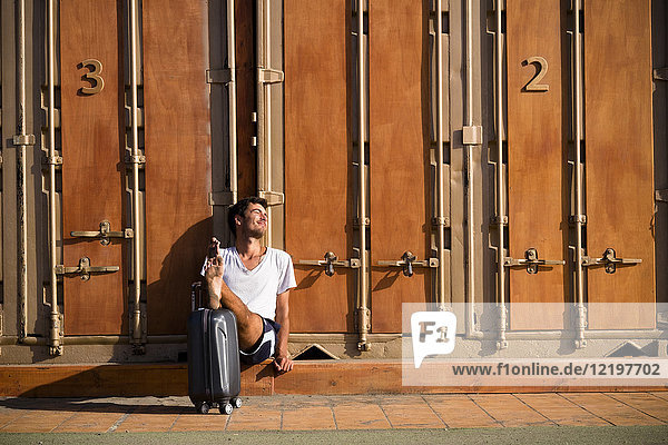 Entspannter Barfußmann mit Rollkoffer vor der Kabine sitzend