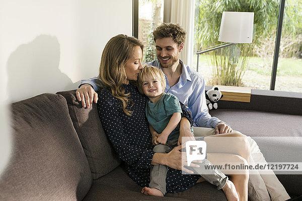 Glückliche Eltern sitzen mit dem Sohn auf dem Sofa zu Hause.