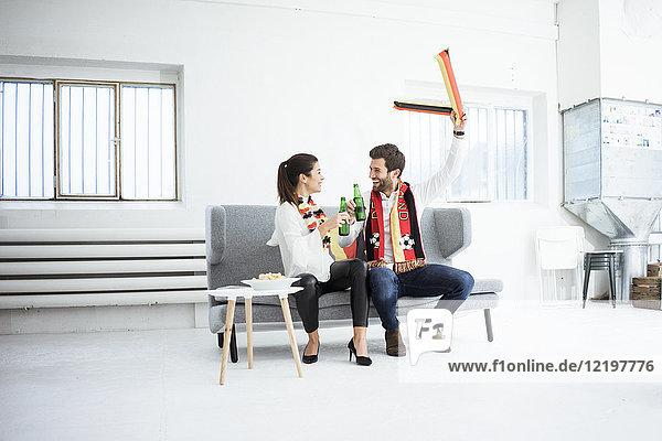 Fröhliches deutsches Fußball-Fanpaar auf der Couch