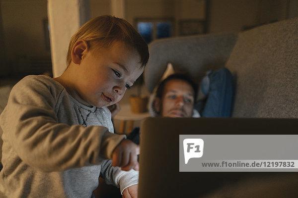 Kleines Mädchen mit Eltern  die den Laptop auf der Couch im Dunkeln anschauen