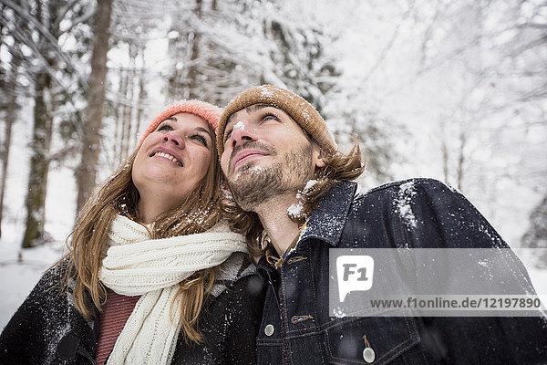 Lächelndes Paar im Winterwald  das den Schneefall beobachtet