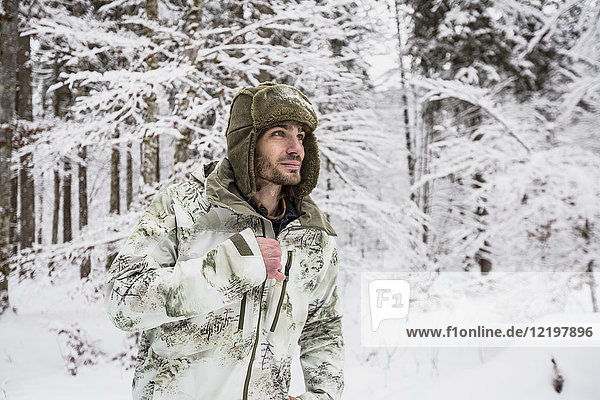 Man in camouflage jacket in winter forest