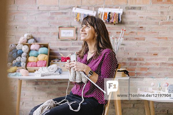 Lächelnde Frau auf dem Stuhl sitzend strickend