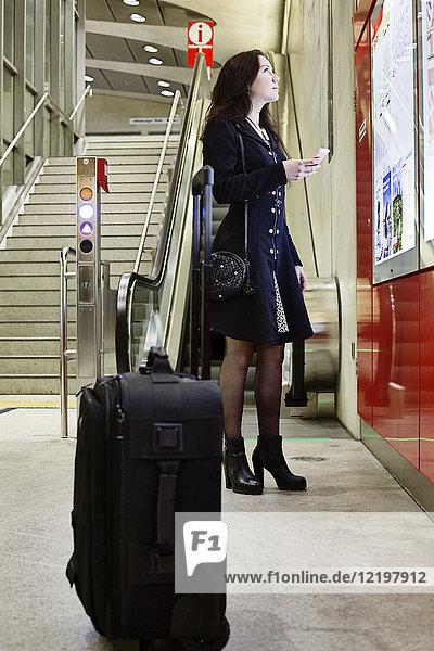 Deutschland  Köln  junge Frau mit Handy auf dem Stadtplan im U-Bahnhof