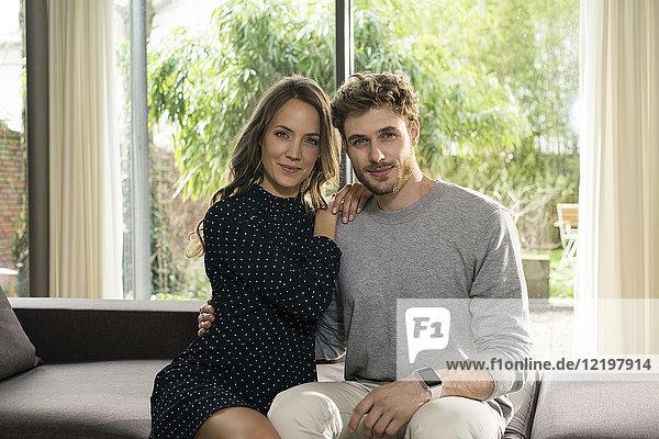 Porträt eines lächelnden Paares auf dem Sofa zu Hause mit Blick auf den Garten