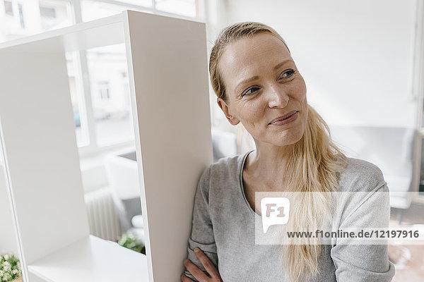 Lächelnde Frau  die sich gegen ein Regal lehnt.
