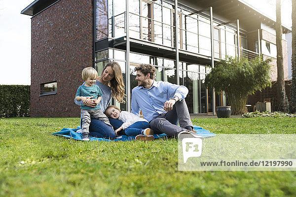 Glückliche Familie auf Decke im Garten vor dem Haus