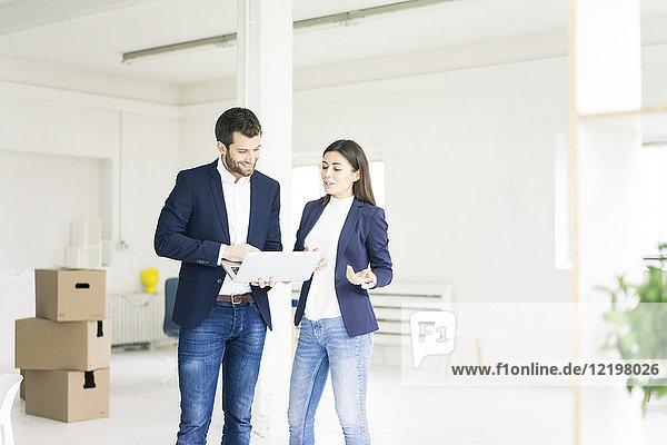 Geschäftsmann und Geschäftsfrau mit Laptop und Kartons im Hintergrund