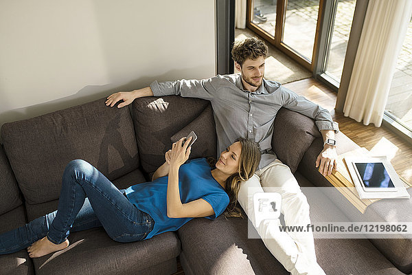 Smiling couple with tablet and smartphone relaxing on sofa at home