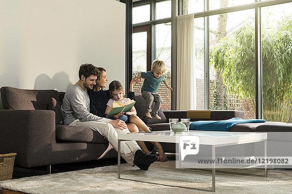 Familie auf dem Sofa zu Hause lesen Buch mit Jungen springen