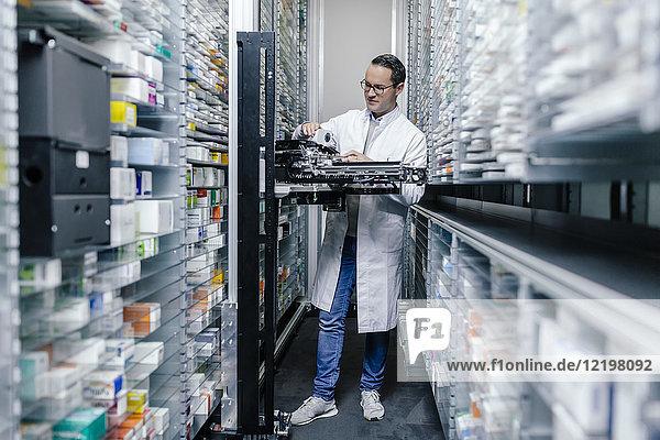 Apothekerin untersucht Kommissioniermaschine in der Apotheke