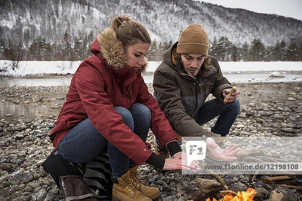 Paar auf einer Reise im Winter wärmende Hände am Lagerfeuer