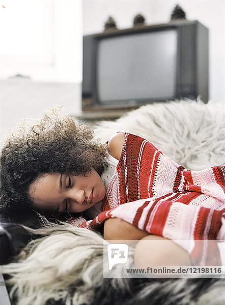 Portrait of little girl sleeping on arm chair in living room