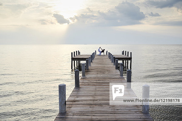 Junge Frau praktiziert Yoga an einem Steg am Meer bei Sonnenuntergang