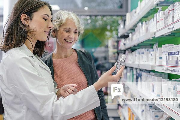 Apothekerin berät Kunden mit Kosmetika in der Apotheke