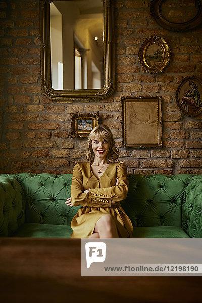 Porträt einer lächelnden  eleganten Frau  die auf einer Couch sitzt. Porträt einer lächelnden, eleganten Frau, die auf einer Couch sitzt.