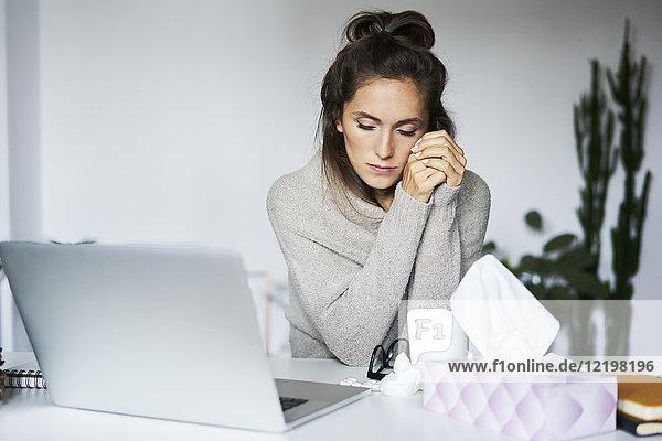 Kranke Frau  die zu Hause am Schreibtisch arbeitet
