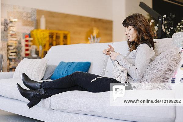 Frau sitzend auf der Couch strickend