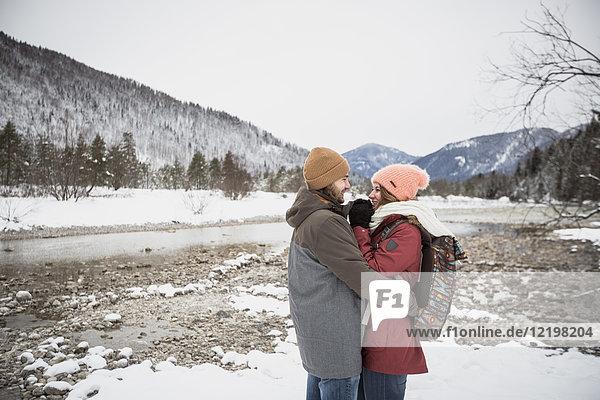 Ein glückliches Paar  das sich im Winter auf einer Reise umarmt.
