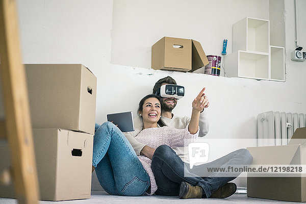 Paar sitzend im neuen Zuhause mit Mann mit VR-Brille