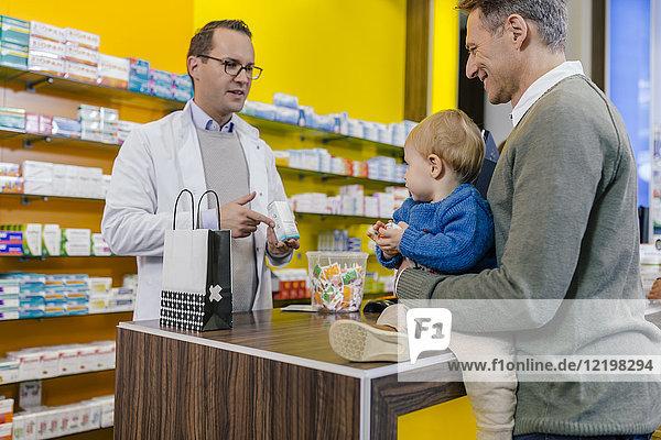 Apothekerin berät Vater mit Sohn in der Apotheke