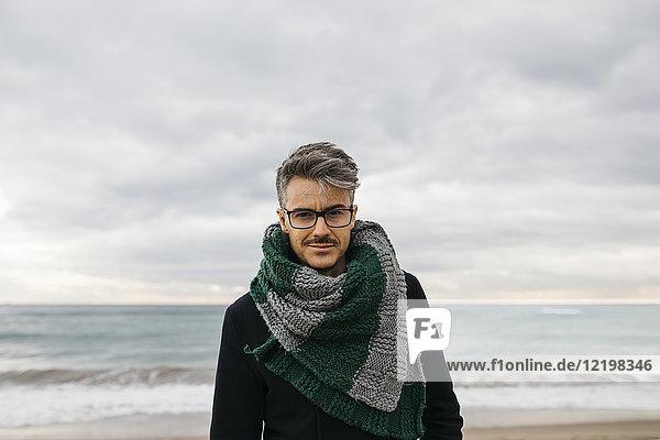 Porträt eines Mannes am Strand mit Strickschal