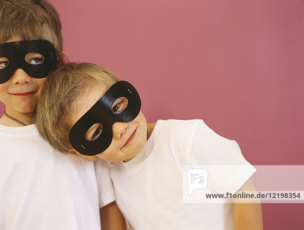 Portrait of two smiling little boys wearing black eye masks