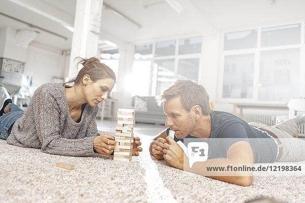 Paar liegt auf dem Boden und spielt Jenga.