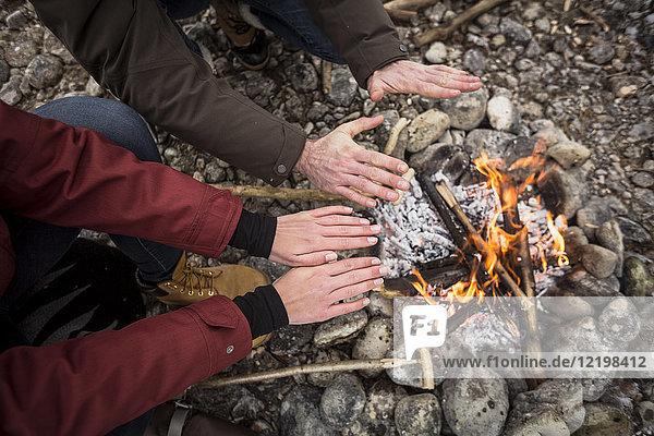 Nahaufnahme von zwei wärmenden Händen am Lagerfeuer