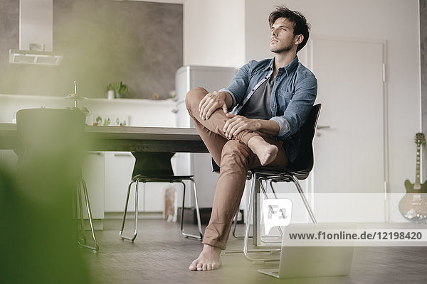 Pensive young man sitting in a loft