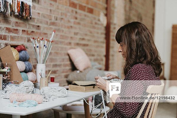 Frau sitzend am Tisch strickend