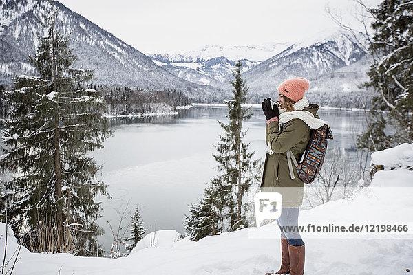 Junge Frau mit heißem Getränk stehend in alpiner Winterlandschaft mit See