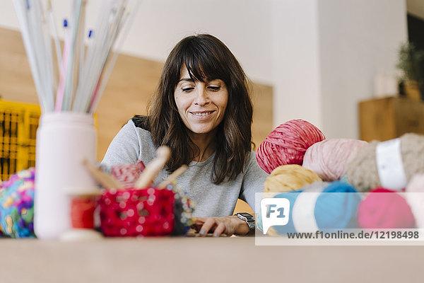 Lächelnde Frau am Tisch mit Strickerei
