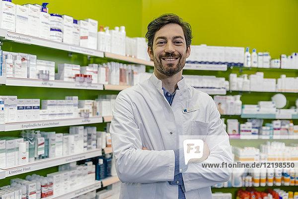 Porträt eines lächelnden Apothekers im Regal mit Medizin in der Apotheke