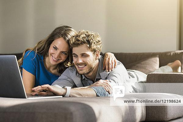 Lächelndes Paar mit Laptop auf dem Sofa zu Hause liegend