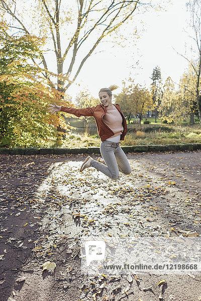 Fröhliche junge Frau beim Springen in der Luft im herbstlichen Park