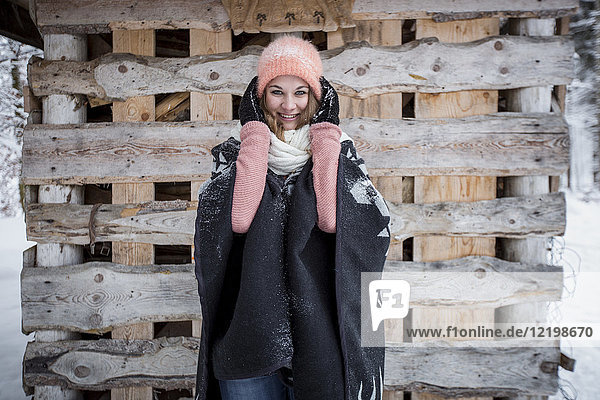Porträt einer lächelnden jungen Frau vor einem Holzhaufen im Freien im Winter