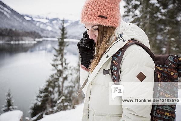 Junge Frau am Handy in alpiner Winterlandschaft mit See