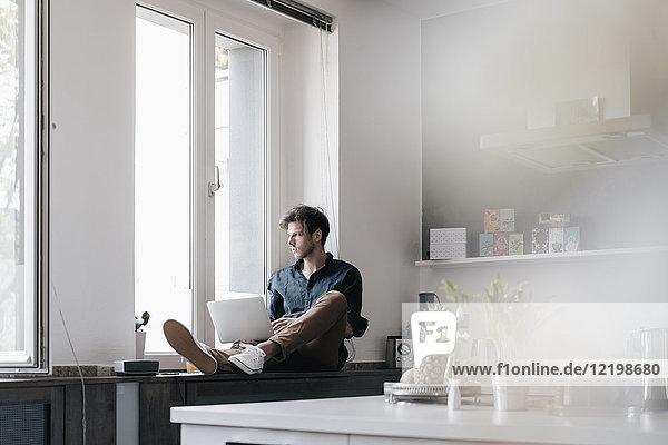 Junger Mann mit Laptop auf der Fensterbank in einem Loft mit Blick aus dem Fenster