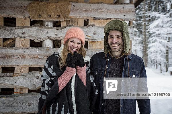 Porträt eines glücklichen Paares vor einem Holzhaufen im Freien im Winter
