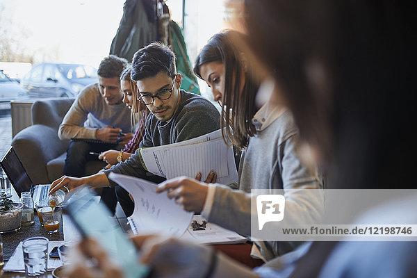 Gruppe von Freunden sitzen zusammen in einem Café mit Laptop und Dokumenten