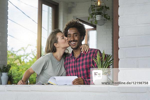 Frau küsst ihren Freund auf die Wange im Cafe