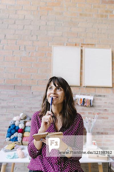 Lächelnde Frau im Strickstudio denkt und macht sich Notizen