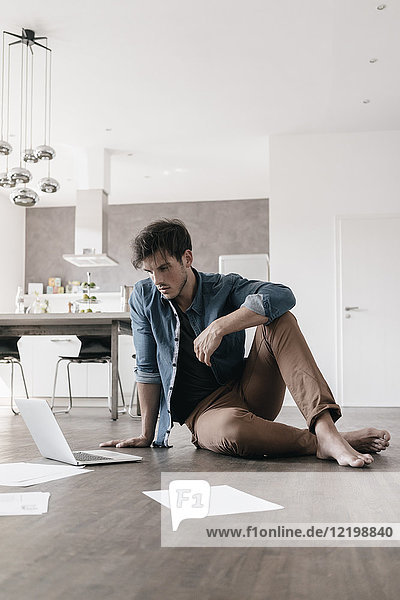 Young man sitting on the floor in a loft using laptop