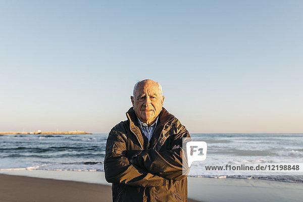 Ein älterer Mann  der am Strand spazieren geht.