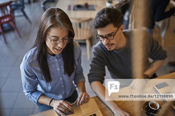 Junge Frau und Mann in einem Café mit Laptop